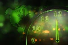 Reloj verde que brilla intensamente con el mapa del mundo Fotos de archivo