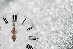 Reloj viejo con los copos de nieve de las estrellas y las luces del día de fiesta Foto de archivo