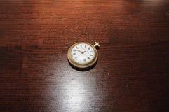 Reloj viejo en el escritorio Imágenes de archivo libres de regalías