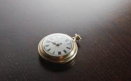 Reloj viejo en el escritorio Imagen de archivo libre de regalías