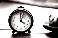Reloj viejo en una tabla de madera Imagen de archivo
