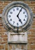 Reloj viejo n una pared de ladrillo Foto de archivo libre de regalías