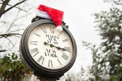 Reloj viejo retro con el sombrero de la Feliz Año Nuevo Nueva York y de Santa Claus del texto en ellos al aire libre en invierno Foto de archivo
