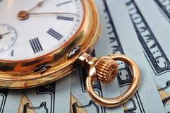 Reloj y dólares de bolsillo Imagen de archivo libre de regalías