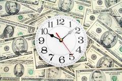 Reloj y dólares de pared imagen de archivo