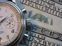 Reloj y dinero Foto de archivo