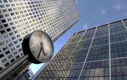 Reloj y edificios de oficinas Fotos de archivo