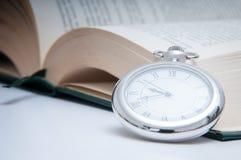 Reloj y libro Imagenes de archivo