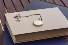 Reloj y libros cerrados Fotos de archivo