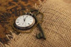 Reloj y llave de bolsillo antiguo en el folio viejo mitad-cubierto con harpillera vieja Tiempo que pasa concepto Concepto de la e imagenes de archivo