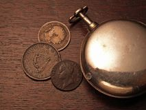 Reloj y monedas fotos de archivo