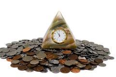 Reloj y monedas de la pirámide Foto de archivo libre de regalías