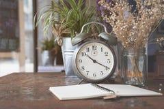Reloj y nota retros con la colocación de la flor blanca imagen de archivo libre de regalías