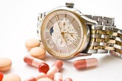 Reloj y píldoras Imágenes de archivo libres de regalías
