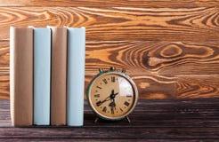 Reloj y pila viejos de libros viejos Foto de archivo libre de regalías