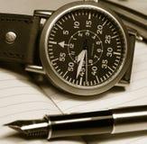 Reloj y pluma Fotos de archivo