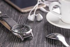 Reloj y teléfono móvil con auriculares y una taza de café en una tabla de madera oscura fotos de archivo