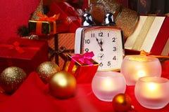Reloj y velas de la Navidad Decoración del ` s del Año Nuevo con las cajas de regalo, las bolas de la Navidad y el árbol Concepto Fotos de archivo