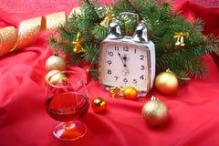 Reloj y vidrio de la Navidad con el coñac o el whisky Decoración del ` s del Año Nuevo con las cajas de regalo, las bolas de la N Imagen de archivo