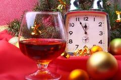 Reloj y vidrio de la Navidad con el coñac o el whisky Decoración del ` s del Año Nuevo con las cajas de regalo, las bolas de la N Foto de archivo