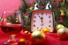 Reloj y vidrio de la Navidad con el coñac o el whisky Decoración del ` s del Año Nuevo con las cajas de regalo, las bolas de la N Foto de archivo libre de regalías