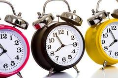 Relojes coloridos en blanco Imagen de archivo