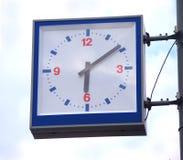 Relojes cuadrados de la calle en el cielo azul con las nubes Fotos de archivo