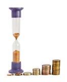 Relojes de arena y columnas de monedas Imágenes de archivo libres de regalías