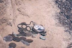 Relojes de bolsillo quebrados y monedas viejas en un acantilado Imagenes de archivo