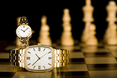 Relojes de oro en tarjeta de ajedrez Fotografía de archivo libre de regalías