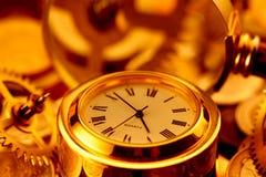 Relojes de oro, monedas, engranajes y lupa Foto de archivo libre de regalías