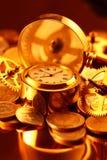 Relojes de oro, monedas, engranajes y lupa Imágenes de archivo libres de regalías