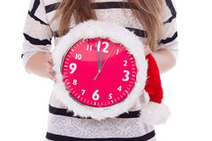 Relojes grandes un sombrero de la Navidad en manos femeninas Año Nuevo 12 horas Imagen de archivo libre de regalías