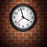 Relojes negros en la pared de ladrillo Imagen de archivo libre de regalías
