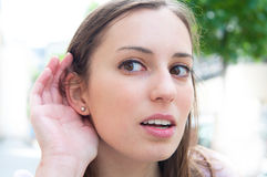 Relying on hand-ear listening young woman Stock Photo