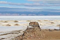 Old jetty on ice. Remainder of wooden jetty in front of old fish factory on Olkhon island, Irkutsk, Russia. Surrounded by ice of Baikal lake in late winter Royalty Free Stock Photo