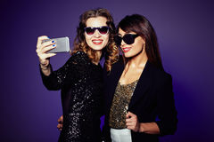 Remaining in Memory the Day. Attractive it girls in trendy sunglasses taking selfie on smartphone before starting to celebrate New Year, waist-up portrait Royalty Free Stock Images