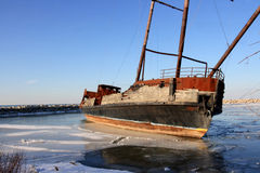 Remaining of a ship after fire. Remaining of a Two Mast Old ship after fire frozen in marina Stock Photo