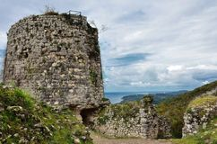 The remains of an ancient observation tower in the mountains. The remains of an ancient observation tower in the mountains, against the blue sky in the clouds royalty free stock photos