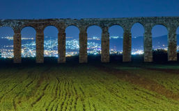 Remains of an ancient Roman aqueduct at night Stock Image