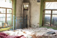 Bedroom in old cottage in abandoned village, Chernobyl Exclusion, Ukraine. Remains of a bedroom in old cottage in abandoned village, Chernobyl Exclusion, Ukraine Royalty Free Stock Images