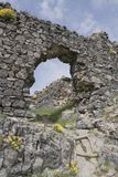 Broken arch way of stone wall. Remains of broken archway of cobble stone building with grass and flowers growing on it Stock Photo