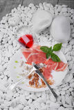 The remains of expensive food on a ceramic plate with a knife and fork on a white stones background. A glass of dry red. A view from above a white plate with stock images