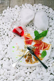 The remains of expensive food on a ceramic plate with a knife and fork on a white stones background. A glass of dry red. A view from above a white plate with stock photos