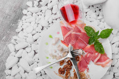 The remains of expensive food on a ceramic plate with a knife and fork on a white stones background. A glass of dry red. A view from above a white plate with stock photography