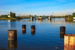 Remains of the old pier. Piles of an old jetty on the background of the railway bridge Royalty Free Stock Image