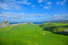 Remains of Peel Castle wall at Peel hill covered with green grass in Isle of Man. Remains of Peel Castle wall constructed by vikings at Peel hill covered with royalty free stock photos