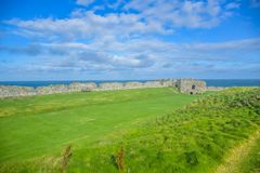 Remains of Peel Castle wall at Peel hill covered with green grass in Isle of Man. Remains of Peel Castle wall constructed by vikings at Peel hill covered with royalty free stock photography