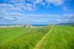 Remains of Peel Castle wall at Peel hill covered with green grass in Isle of Man. Remains of Peel Castle wall constructed by vikings at Peel hill covered with stock photography