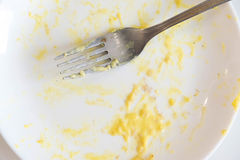 Remains of a plate of ravioli with a fork. White dirty dish after pasta spaghetti with meat and tomato sauce. Bechamel. Sauce stains on the dish Royalty Free Stock Photo